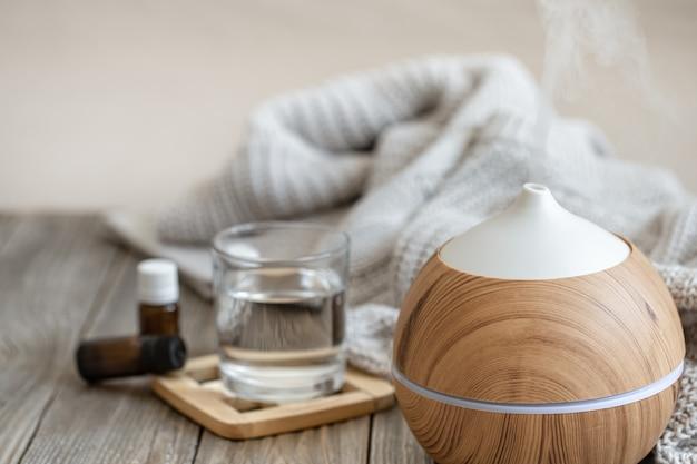 Moderner aromaöldiffusor auf holzoberfläche mit strickelement, wasser und ölen in gläsern.