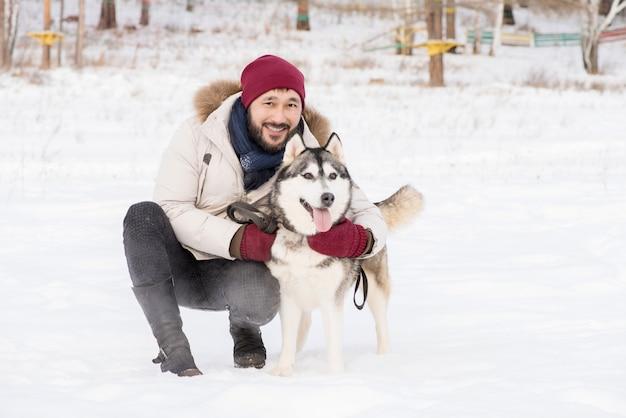 Moderner asiatischer mann mit husky-hund