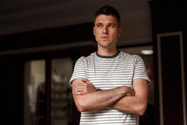 Moderner attraktiver junger mann in einem modischen gestreiften t-shirt mit einer stilvollen frisur, die in einem dunklen studio aufwirft.