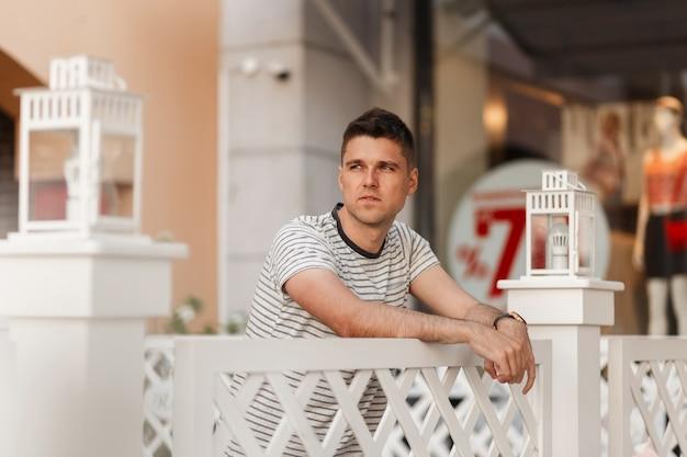 Moderner attraktiver junger mann in einem modischen gestreiften t-shirt mit einer stilvollen frisur ruht nahe einem hölzernen weißen zaun