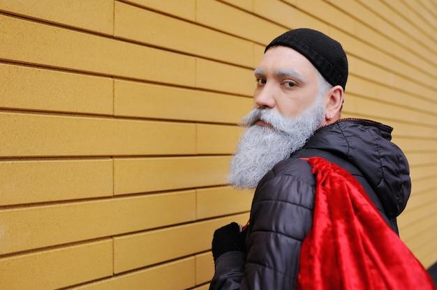 Moderner attraktiver weihnachtsmann mit einem schönen grauhaarigen bart mit einer roten tasche mit geschenken