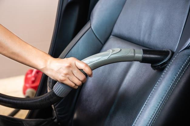 Moderner autoinnenraum mit staubsauger säubern. vakuum handhaben