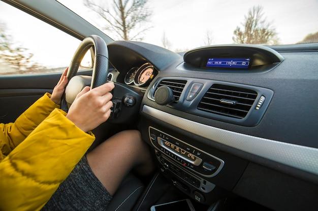Moderner autoinnenraum mit weiblichen fahrerhänden am lenkrad. sicheres fahrkonzept.