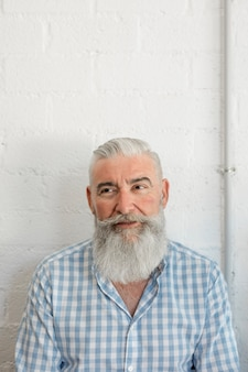 Moderner bärtiger älterer mann im hemd im salon