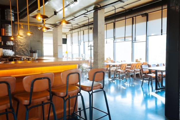 Moderner barständer. schöner moderner barstand in der nähe von tischen in einem modernen, geräumigen restaurant?