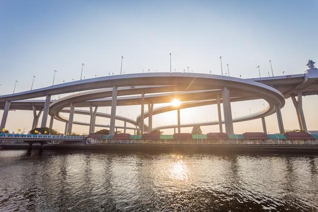 Moderner beton überbrückt die wege über den großen fluss in der sonnenuntergangzeit mit sonnenlicht.