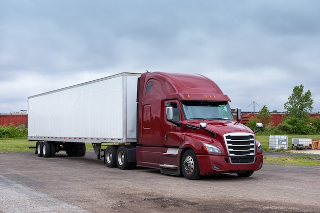 Moderner big rig semi truck für langstrecken mit einer hohen kabine zur verbesserung der aerodynamischen eigenschaften beim transport eines trockenen van-sattelanhängers mit gewerblicher fracht auf der straße.