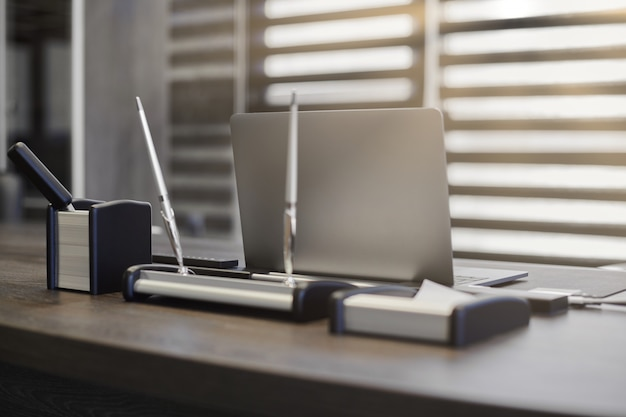 Moderner büroarbeitsplatz. business-laptop am arbeitsplatz für chef, chef oder andere mitarbeiter. notebook auf arbeitstisch. büro großunternehmen. licht durch halboffene jalousien