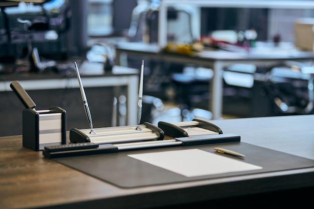Moderner büroarbeitsplatz im großkonzern. bequemer arbeitstisch mit schreibwaren, ledersessel. chef, chef, vorgesetzter oder betriebsleiter.