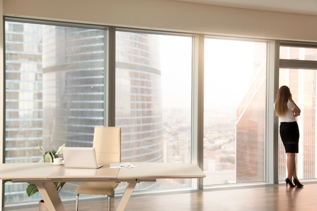 Moderner büroinnenraum mit dem weiblichen schattenbild, das am in voller länge fenster steht