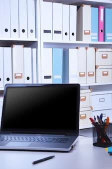Moderner büroinnenraum mit laptop, stühlen und bücherschränken