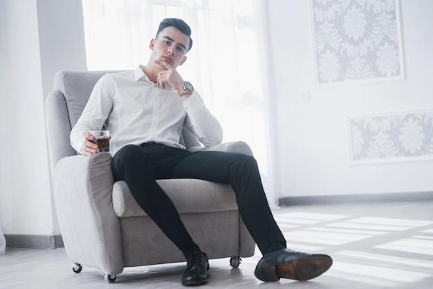 Moderner business-stil. junger eleganter kerl im weißen anzug sitzt auf dem stuhl und hält glas mit alkohol.
