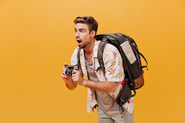 Moderner cooler junger mann mit sonnenbrille in modischer sommerkleidung, der wegschaut und die kamera an der orangefarbenen wand hält