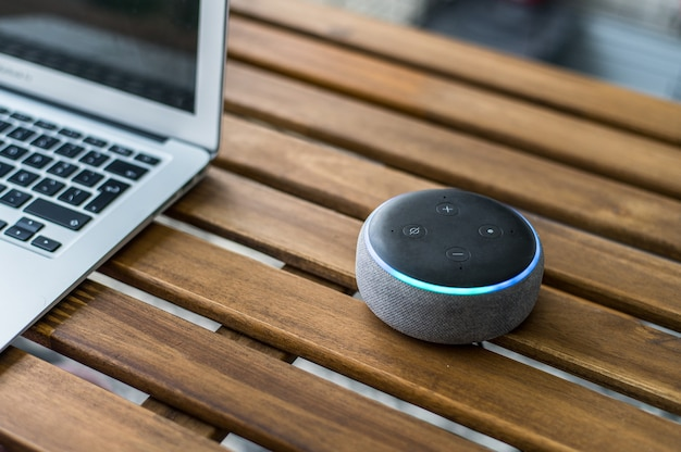 Moderner drahtloser intelligenter lautsprecher platziert auf holztisch nahe verschwommenem laptop zu hause