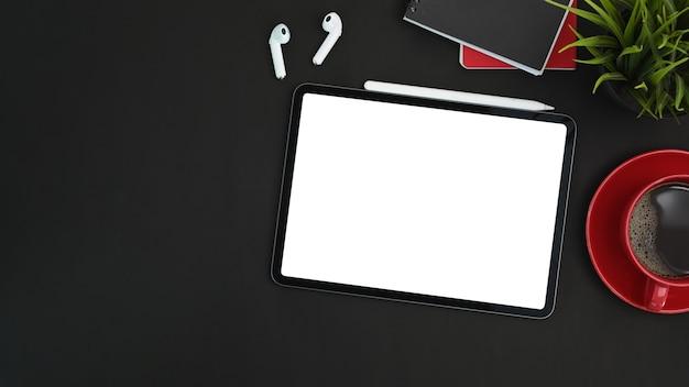 Moderner dunkler arbeitsplatz mit digitalem tablet, stylus-stift, kopfhörer und kaffeetasse auf schwarzem leder. Premium Fotos