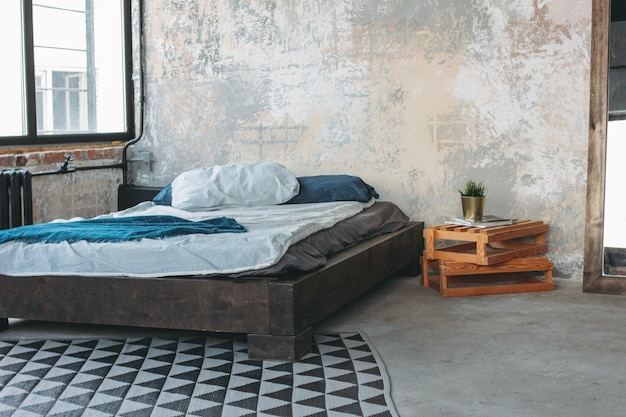 Moderner eco dachbodeninnenraum im schlafzimmer, konkreter boden, bett, minimalismus