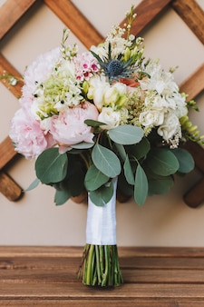 Moderner eleganter brautstrauß mit rosen, pfingstrosen und eukalyptusblättern