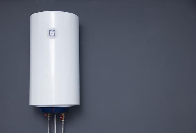 Moderner elektrischer boiler an einer grauen einfachen wand. weißwasser-heizung. platz für text.