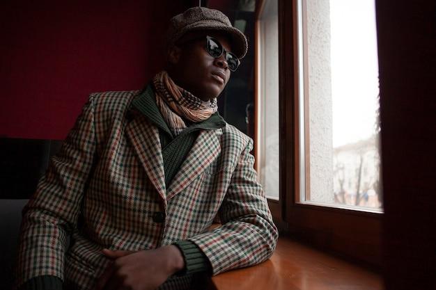 Moderner erwachsener mann mit sonnenbrille und hut