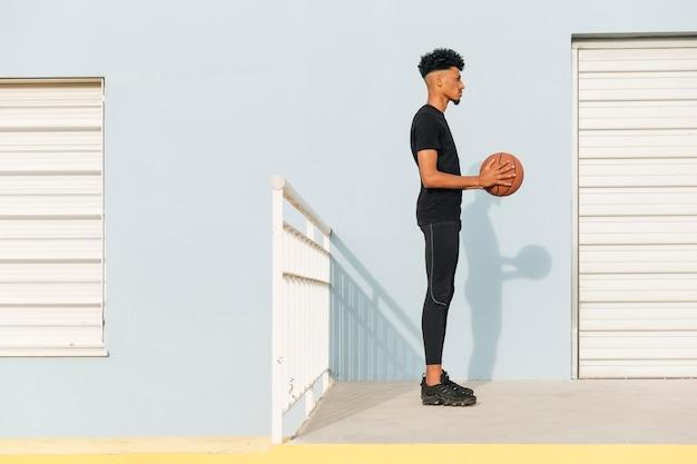 Moderner ethnischer mann mit basketball auf straße