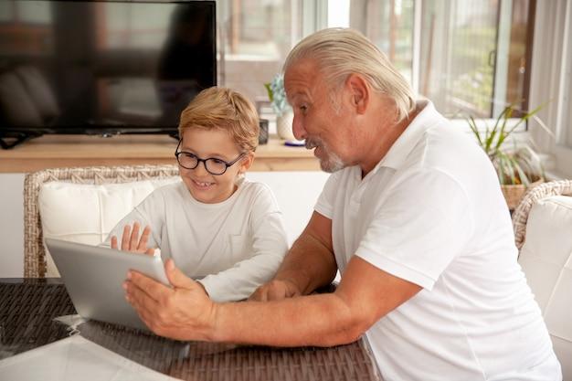 Moderner familienjunge und senior, der video-chat mit anwendung auf tablette hat