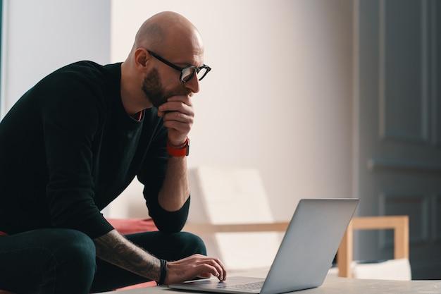 Moderner fokussierter mann mit bart und brille, die an einem laptop arbeiten