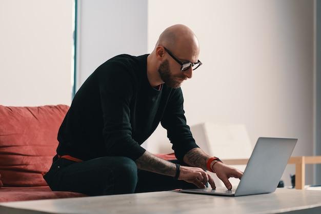 Moderner fokussierter mann mit bart und brille, die an einem laptop in einem modernen innenraum arbeiten