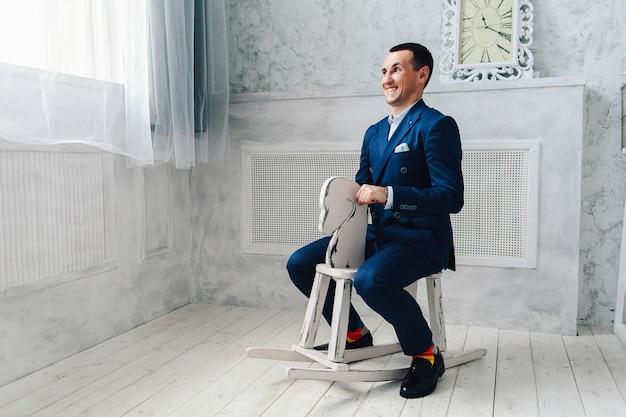 Moderner fröhlicher mann in einem blauen anzug sitzt auf einem spielzeugpferd.