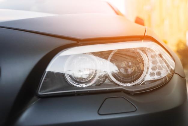 Moderner geführter scheinwerfer des dunklen autos auf straße