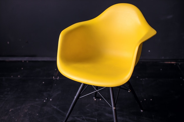 Moderner gelber stuhl im parkettholzboden des schwarzen rauminnenraums.