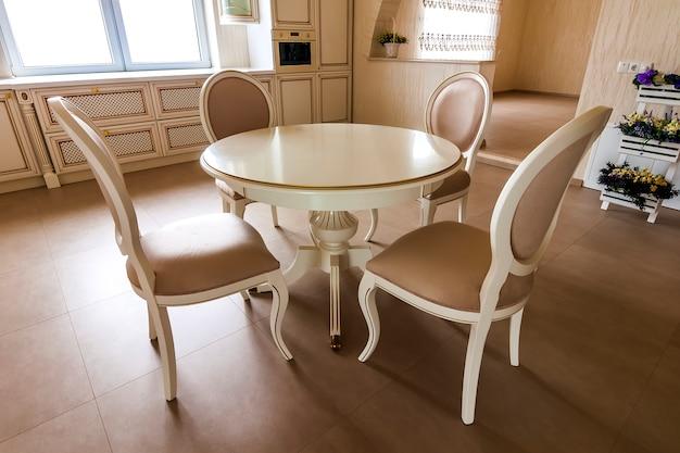 Moderner gepaßter küchenluxusinnenraum. küche im luxushaus mit beige cabinetry. tisch und stühle