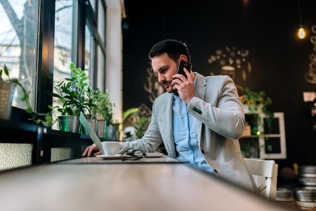 Moderner geschäftsmann, der auf einem smartphone beim arbeiten an laptop im café spricht.