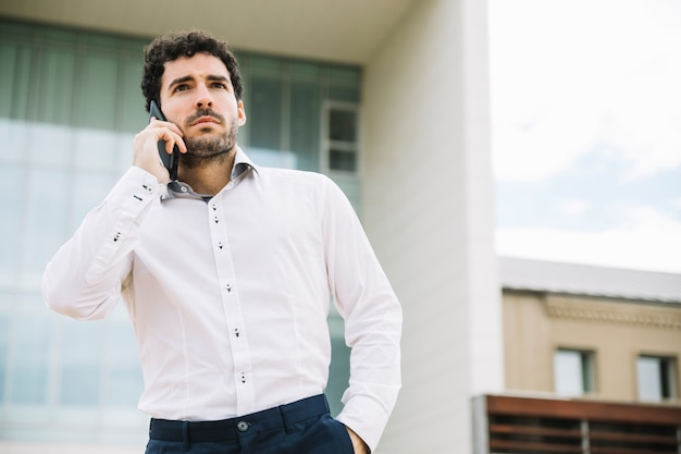 Moderner geschäftsmann, der draußen telefonanruf macht