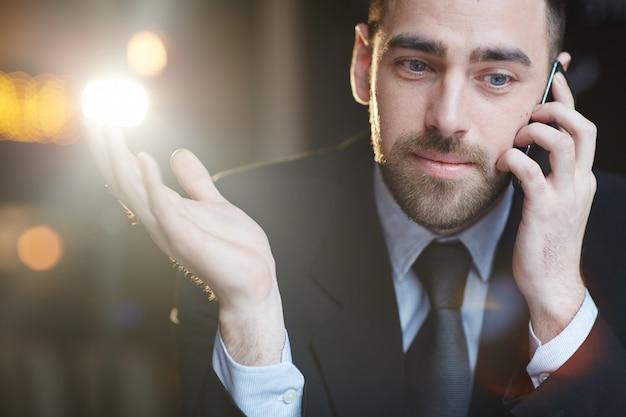 Moderner geschäftsmann, der durch smartphone spricht