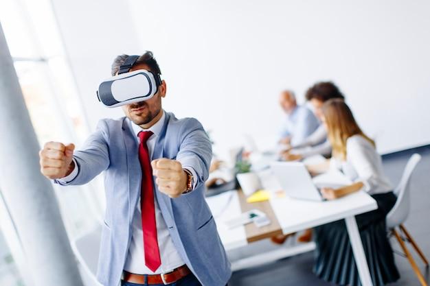 Moderner geschäftsmann mit kopfhörern der virtuellen realität im büro