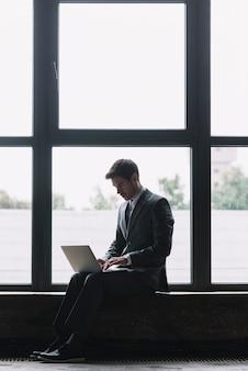 Moderner geschäftsmann mit laptop auf seinem schoss sitzend vor fenster