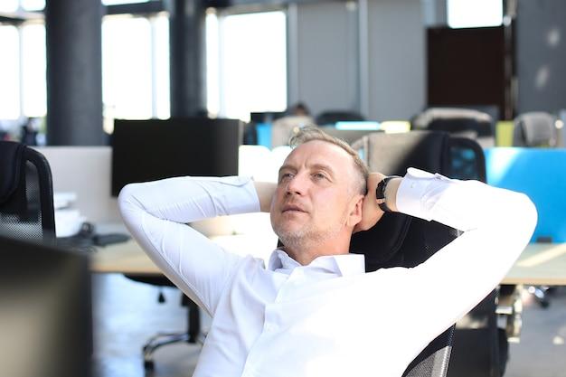 Moderner geschäftsmann mittleren alters, der die hände hinter dem kopf hält und beim sitzen im büro lächelt.