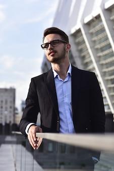 Moderner geschäftsmann. selbstbewusster junger mann im vollen anzug, der draußen mit stadtbild im hintergrund steht standing