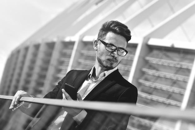 Moderner geschäftsmann. selbstbewusster junger mann in vollem anzug, der mit einem smartphone im freien steht, mit stadtbild im hintergrund