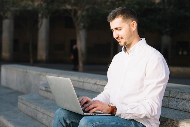 Moderner geschäftsmann unter verwendung des laptops draußen