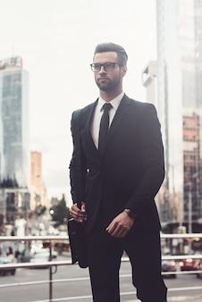 Moderner geschäftsmann unterwegs. selbstbewusster junger und gutaussehender mann im vollen anzug, der entlang geht