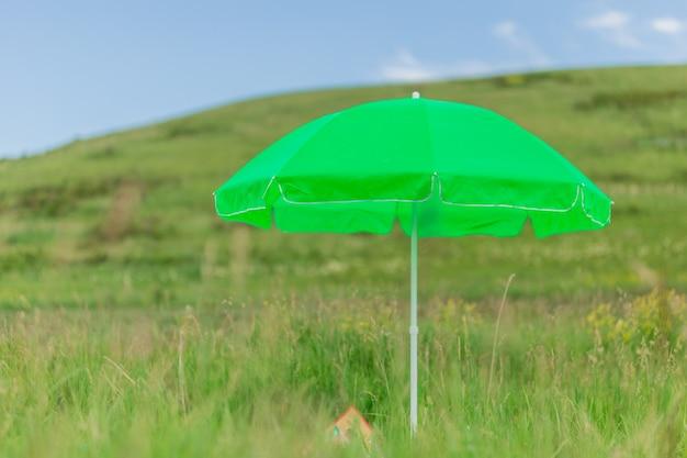 Moderner grüner neonregenschirm für sonne auf strand gegen meer