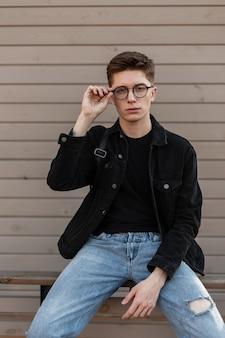 Moderner gutaussehender junger mann in stylischer jeanskleidung glättet trendige brillen
