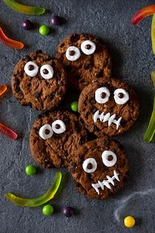 Moderner halloween-hintergrund. halloween-kekse. lustige monster aus keksen mit schokolade auf dem tisch