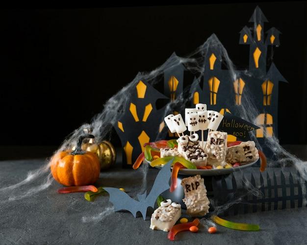 Moderner halloween-hintergrund. halloween schokoriegel: lustige monster aus keksen mit schokolade und geister marshmelow nahaufnahme auf dem tisch