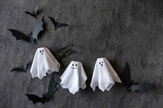 Moderner halloween-hintergrund mit fledermäusen und geistern auf dunklem hintergrund