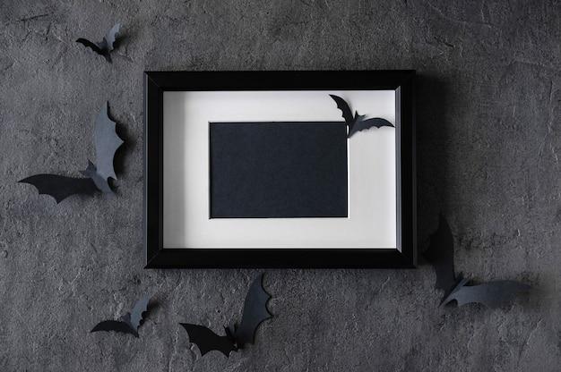 Moderner halloween-hintergrund mit fledermäusen und schwarzem rahmen auf dunklem hintergrund