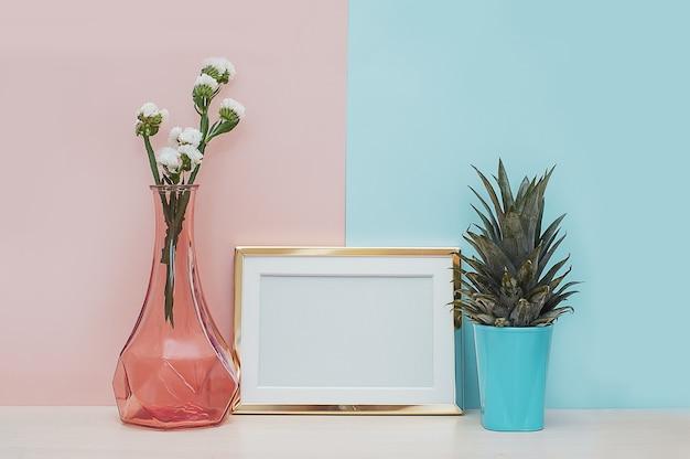 Moderner hauptdekorspott oben mit goldenem fotorahmen, vase und tropischer anlage auf rosa blauer rückseite