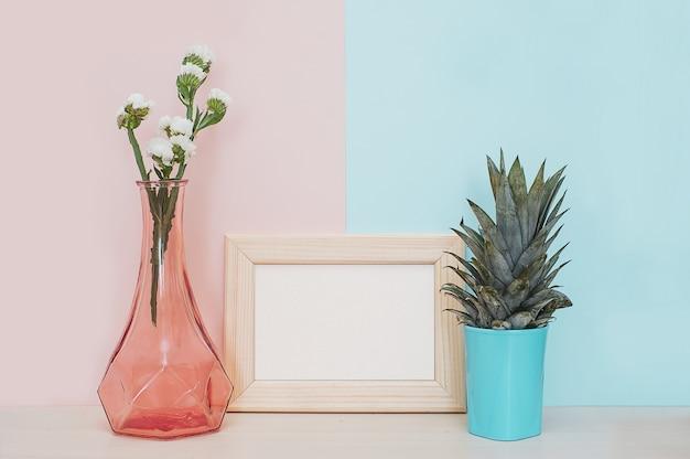 Moderner hauptdekorspott oben mit hölzernem fotorahmen, vase und tropischer anlage auf rosa blauem ba