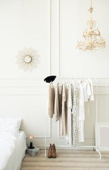 Moderner heller schlafzimmerinnenraum. kleiderbügel mit damenbekleidung.